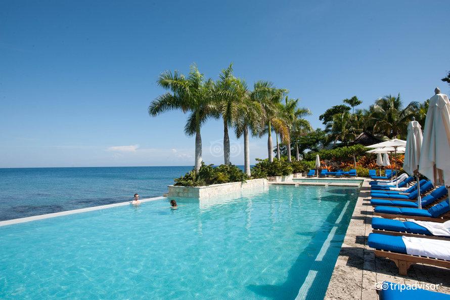 Designhotell: Infinity pool, palmer og blå himmel på Round Hill Hotell and Villas i Jamaica.
