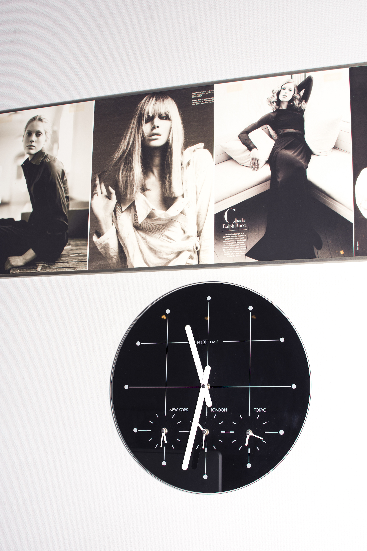 Close-up av en klokke på veggen som viser tre tidssoner.