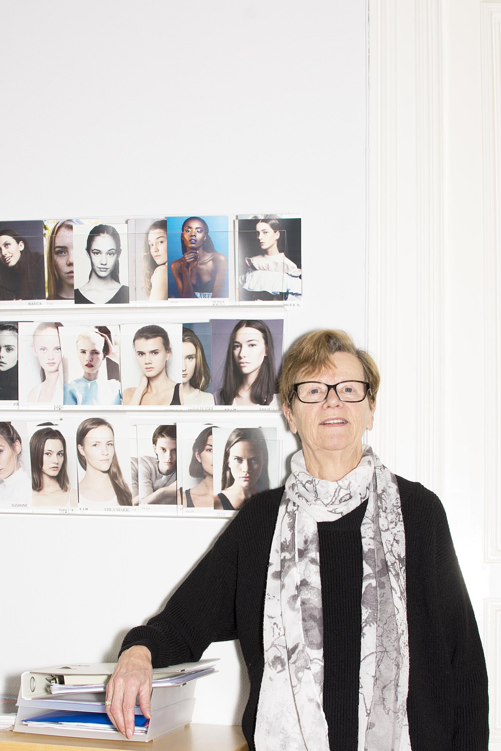 Portrett av Eivor Øvrebø med bilder av modellene hengende på veggen bak henne.