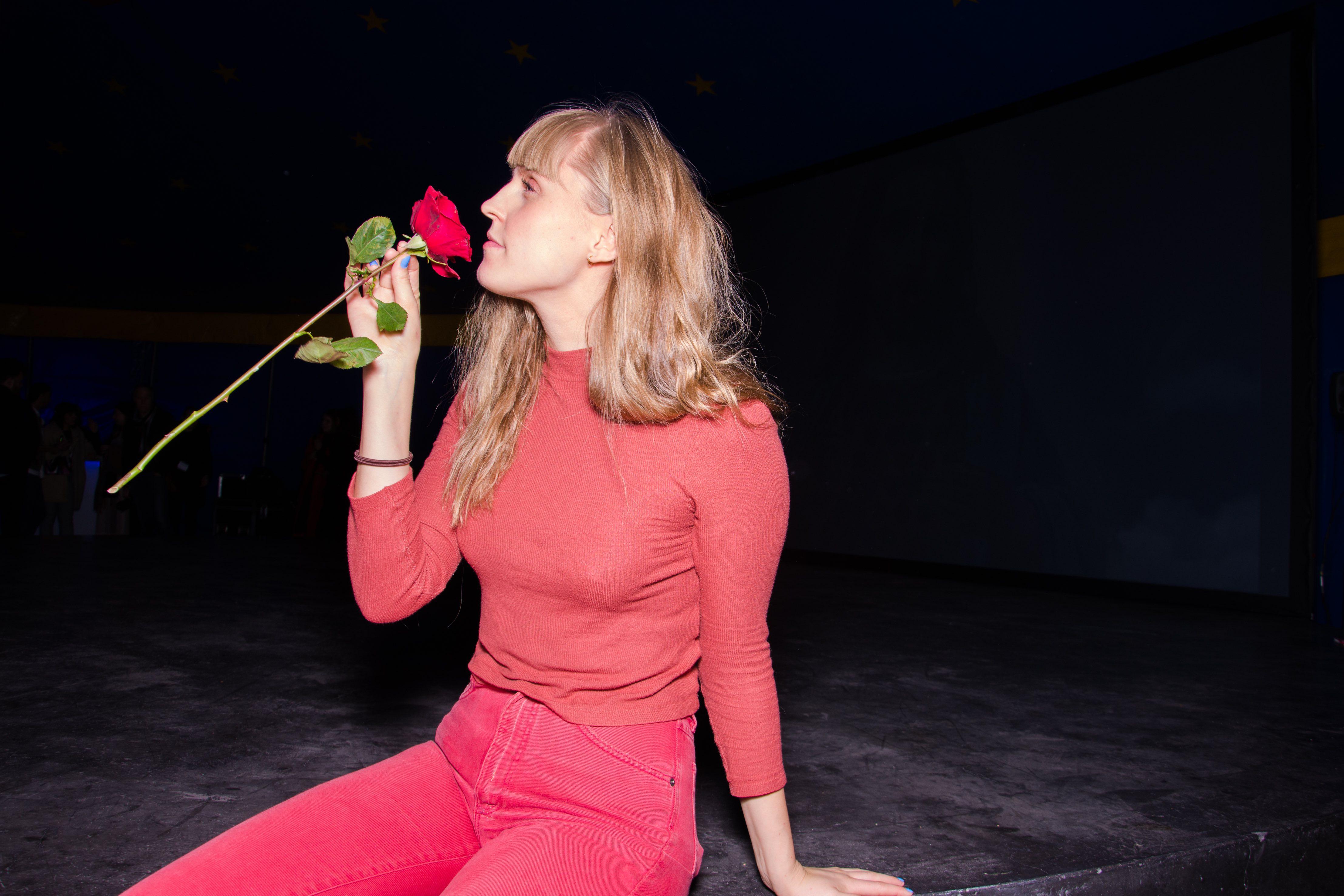 Jente som lukter på rose