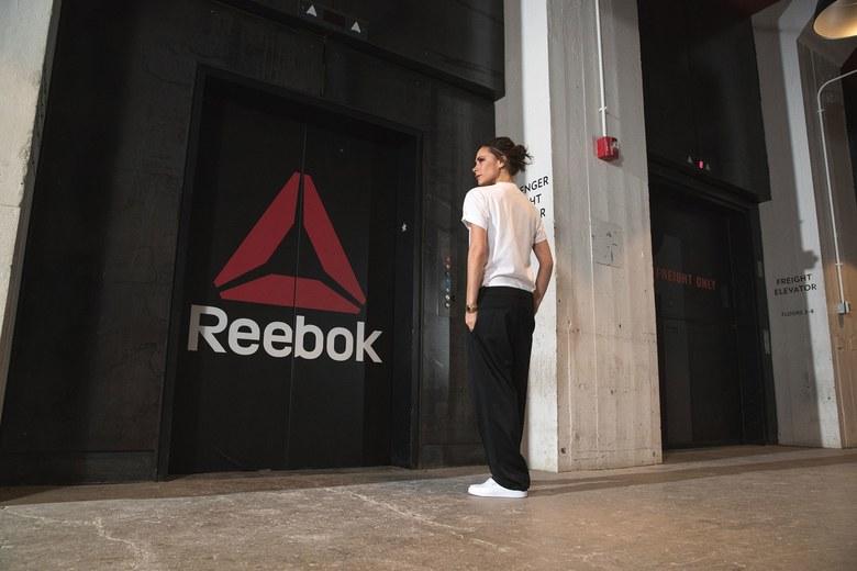 Victoria Beckham i hvite sneakers foran Reebok-vegg