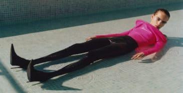 En kvinne som ligger i et basseng fullt påkledd i moteklær